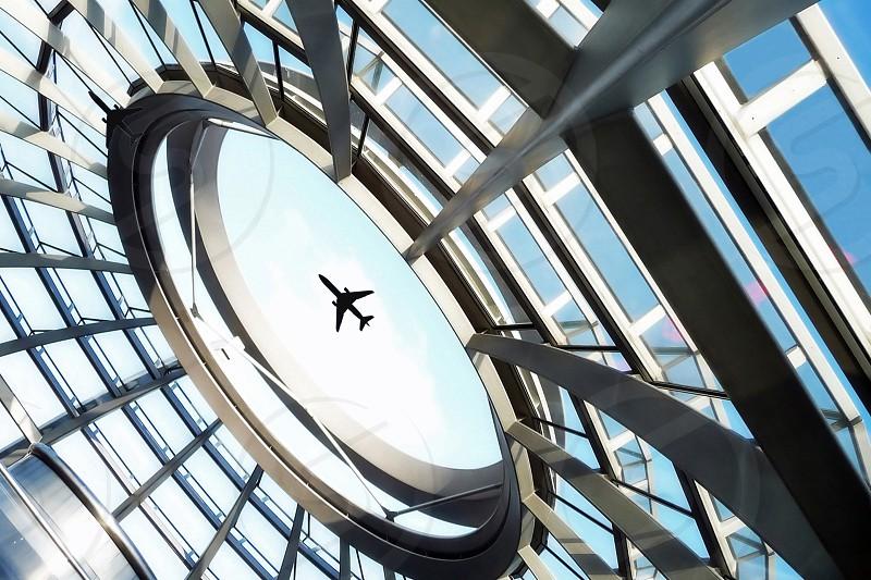 airplane passes near glass round window photo