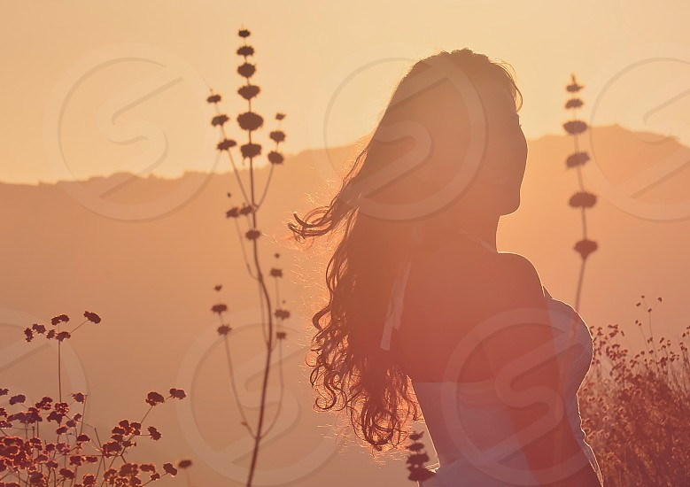 woman wearing white halter neck dress surrounded with flowers during sunset photo