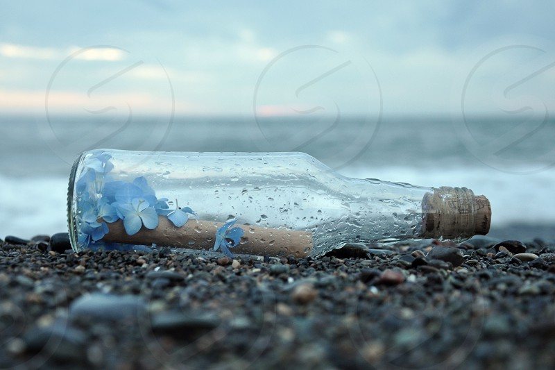 clear glass bottle on black sand photo