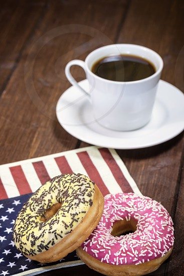 Pair of American donuts are lying on a napkin  with the design of the American flag. Cup of coffee is in the background. Photo is designed as a vintage with dark edges. photo