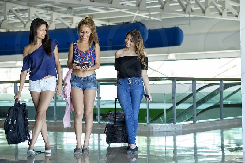 Group of 3 female teenagers with luggage at airport terminal photo