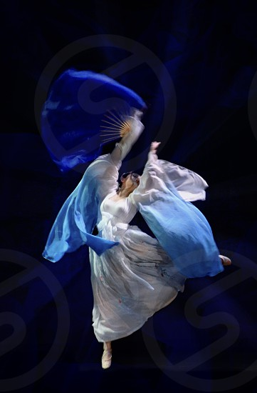Freedom dancer jumping flying high in the air performing on stage in blue flowing costume photo