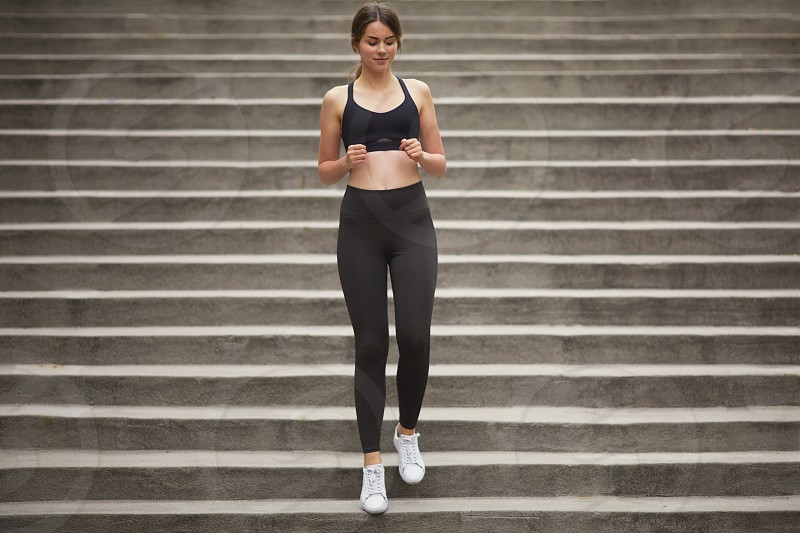 Fit pretty girl running up stairs with city background photo