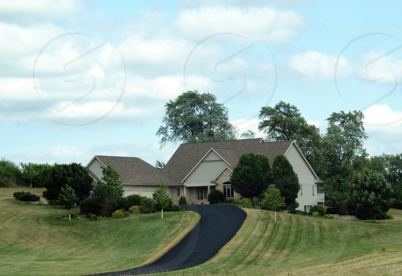 Tan countryside home with black asphalt driveway photo