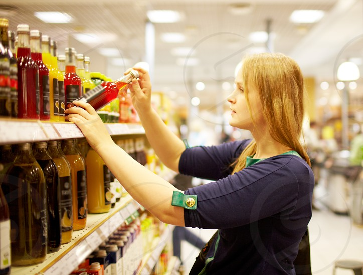 Young blonde woman is choosing juice in the supermarket photo
