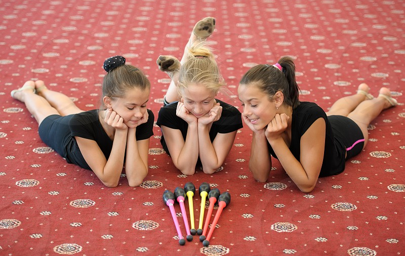 Three young female gymnasts lying on the floor and looking at Indian clubs photo
