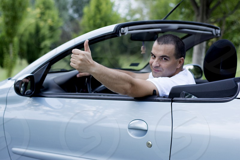 Man giving thumbs up for traveling in convertible car photo