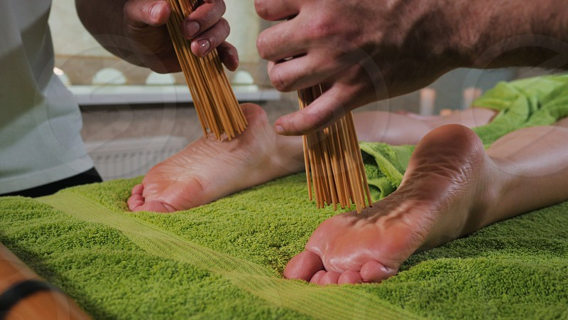 Two male masseurs working with woman. Japanese feet massage with bamboo sticks in the spa salon. People beauty healthy lifestyle and relaxation concept. photo
