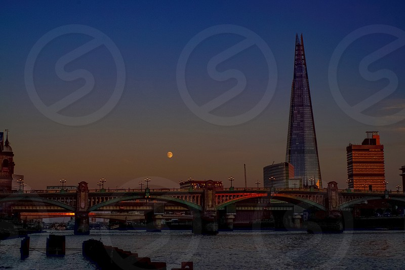 Southwark Bridge in London with the Shard in sight and the moon on view late at sunset photo