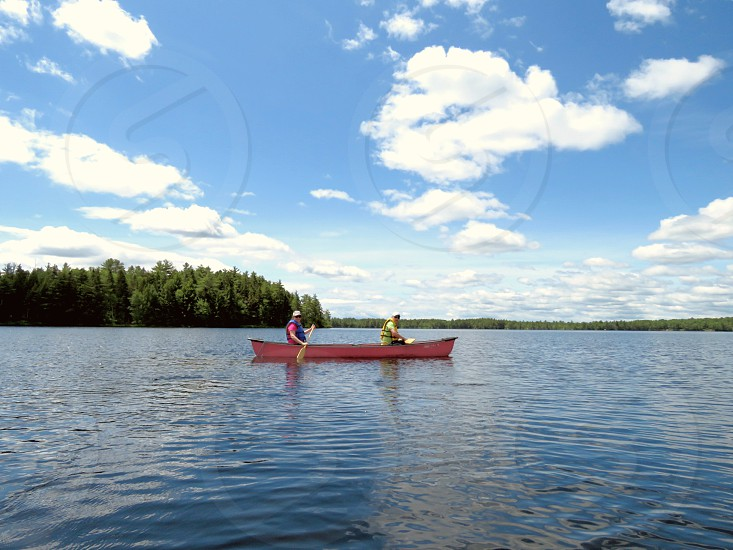 canoe 2 people paddling island trees lake blue skies summer landscape red canoe photo