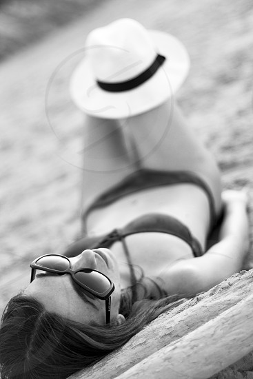 woman in bikini and sunglasses laying in sand with hat on knee photo