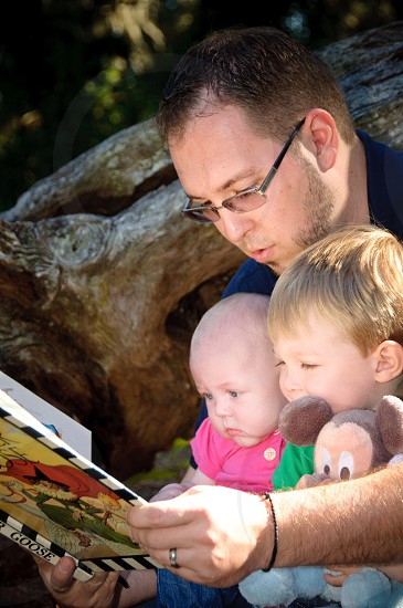man reading a book together with 2 kids photo