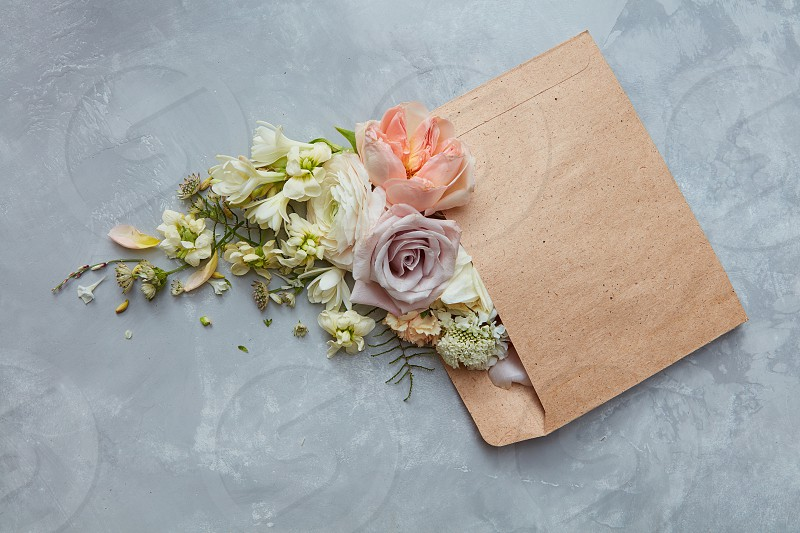 Romantic envelope with flowers on the stone gray background. flat lay photo