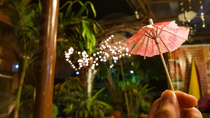 Cocktail umbrella held in front of light trails photo