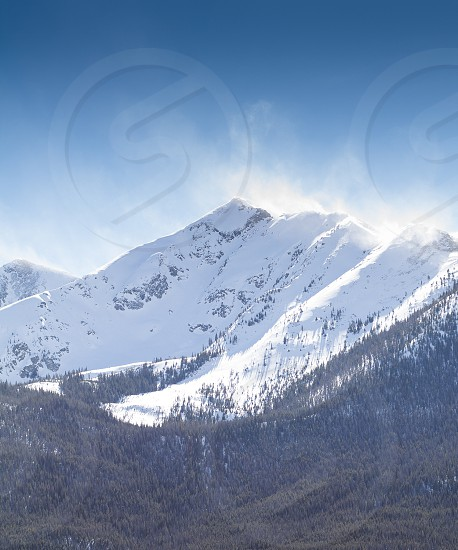 Wind blown snow covered mountain photo