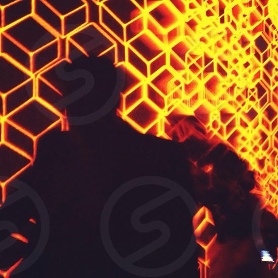 black man silhouette  near a orange neon light photo