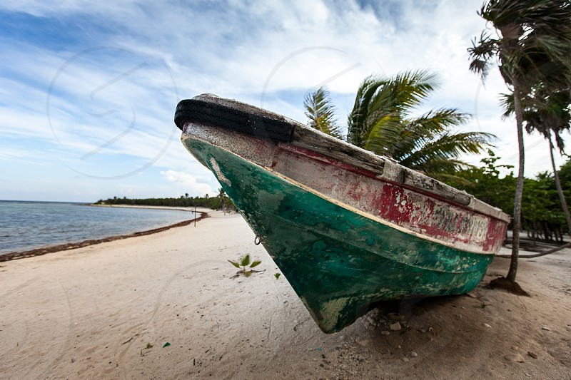 A small weathered rustic green and red row boat / ship / vessel beached on the sandy tropical shore island shows signs of adventure on the seas / ocean / water. photo