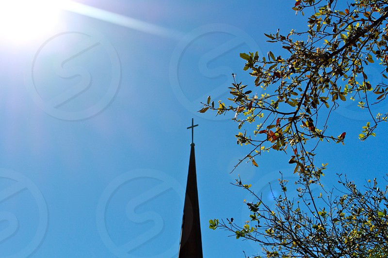 black cross on top of chapel under clear blue sky during day photo