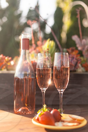 two champagne flutes filled with rose wine next to the bottle on a wood table surrounded by plants and trees under the sun photo