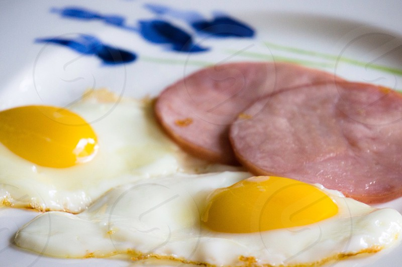 two sunny side up eggs and two sliced fried meats photo