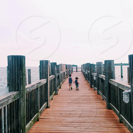 Young brothers hold hands and walk on a boardwalk photo