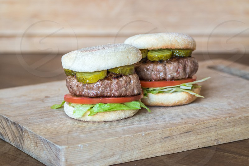 British beef burgers in English muffin buns with gherkins beef tomatoes and shredded lettuce. Presented on a wooden chopping board photo