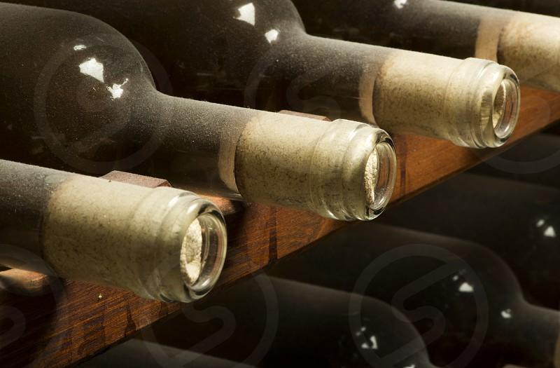 Wine bottles on shelf. Wine cellar. Close up wine bottles. photo
