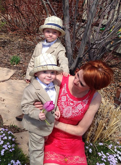 woman in white floral printed red tank dress holding boy in beige tuxedo photo