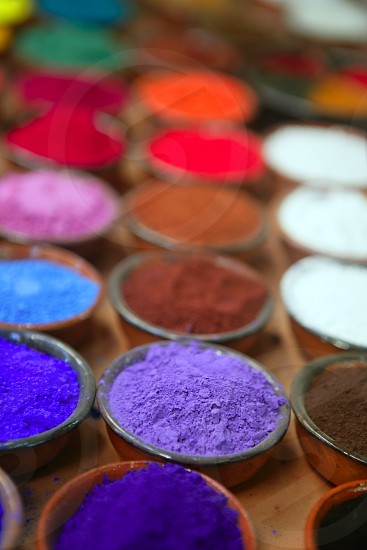 colorful powder pigments in rows in clay bowls photo