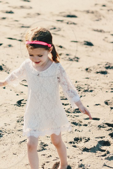 a young girl walking on the beach in the summer time with a white dress and a pink headband with pig tails photo