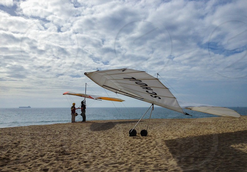 Hang glider school on a beach/bluff overlooking the Pacific Ocean.  photo