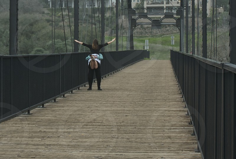 Woman Leaping Into Arms Of Boy Friend On Bridge photo