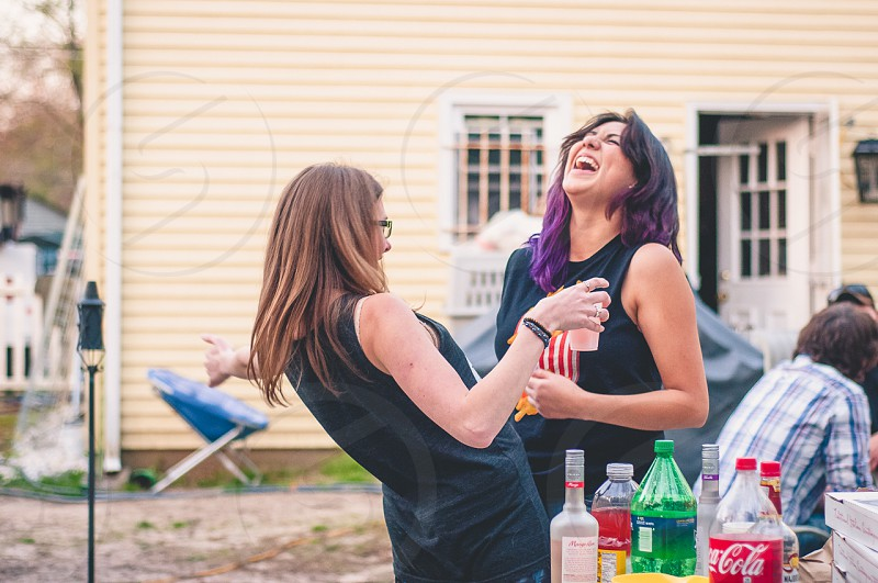 2 woman wearing black tank top smile together photo