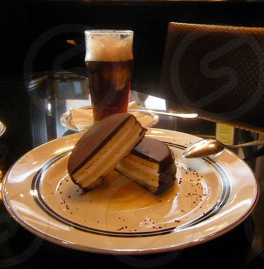 Root beer float and chocolate marshmallow snack pie on white plate on black table with chair photo