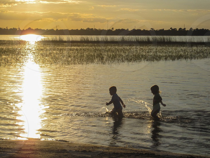 Kids lake splash sunset backyard silhouette children play playing fun photo