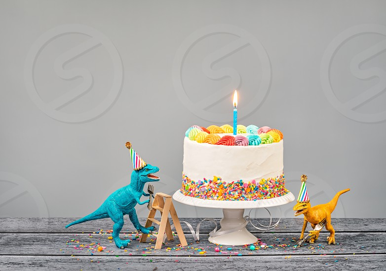 Hungry toy dinosaurs wearing hats and holding forks next to a birthday Cake on a gray background photo