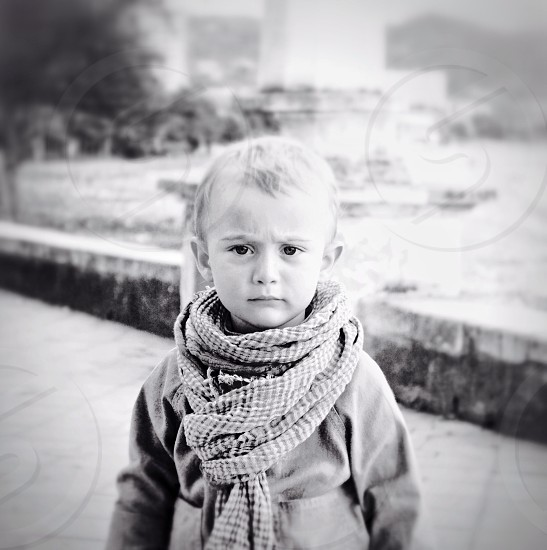 grayscale photography of frowning boy wearing scarf and long sleeve shirt during daytime photo