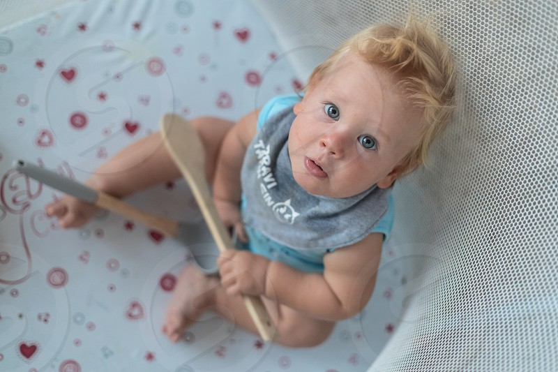 Blue eyed baby looking towards camera and holding cookware in hand photo