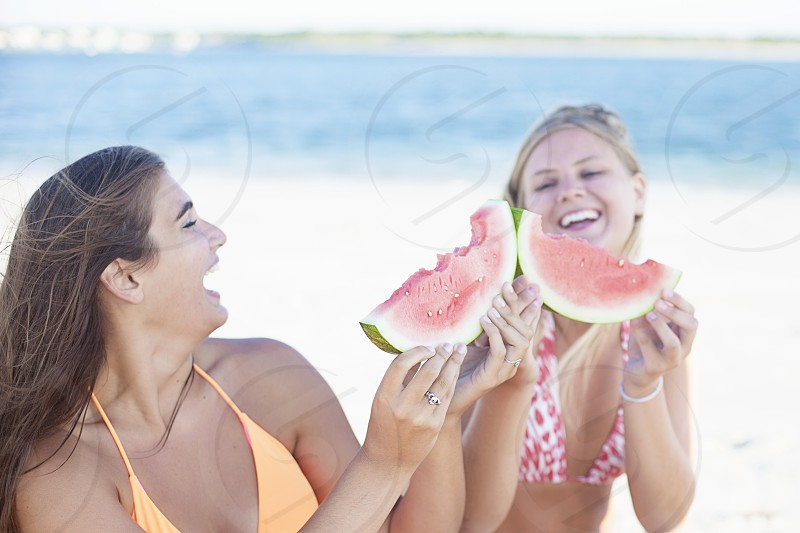 two girls in bathing suits eating watermelon photo
