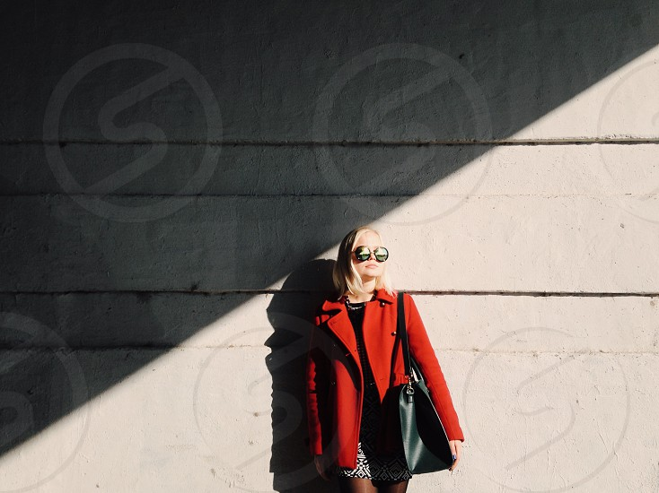 woman wearing round sunglasses and red blazer with black leather tote bag standing against grey wall hit by sunlight photo