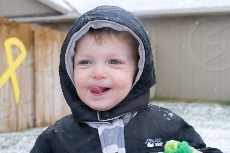 baby in black and grey old navy hoodie licking lips photo