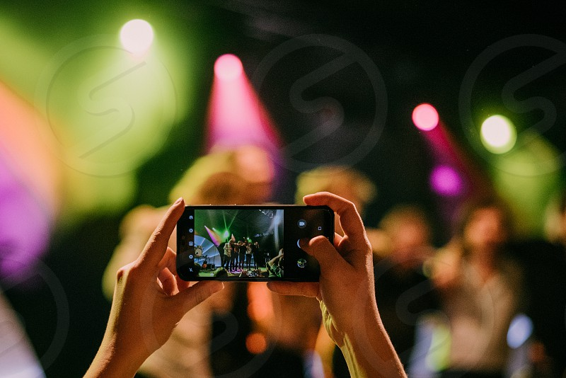 Fan taking a picture with her phone during a music show. photo