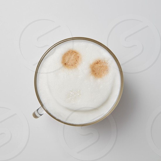 Hot cappuccino in a glass cup with a smile face on a gray background with space for text. Top view photo