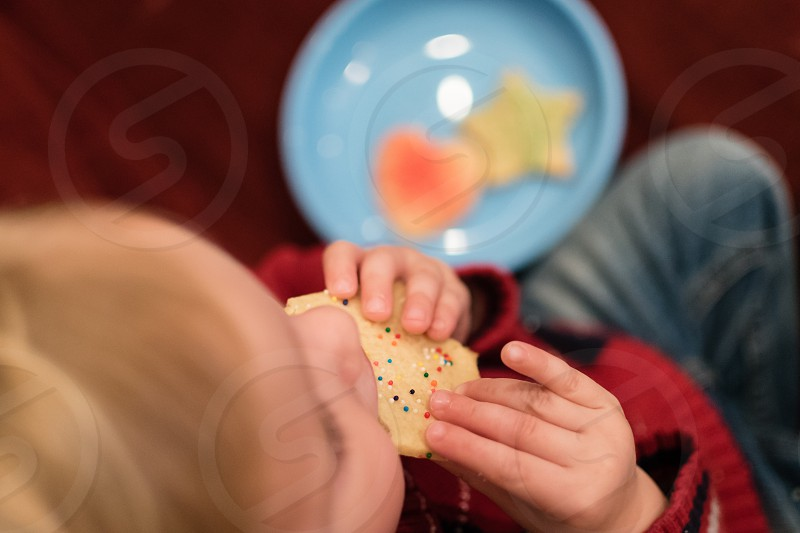 Top view of child eating a cookie photo