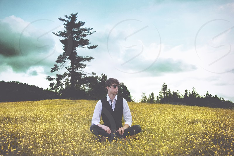 man sitting in a middle of a yellow flowered field  photo
