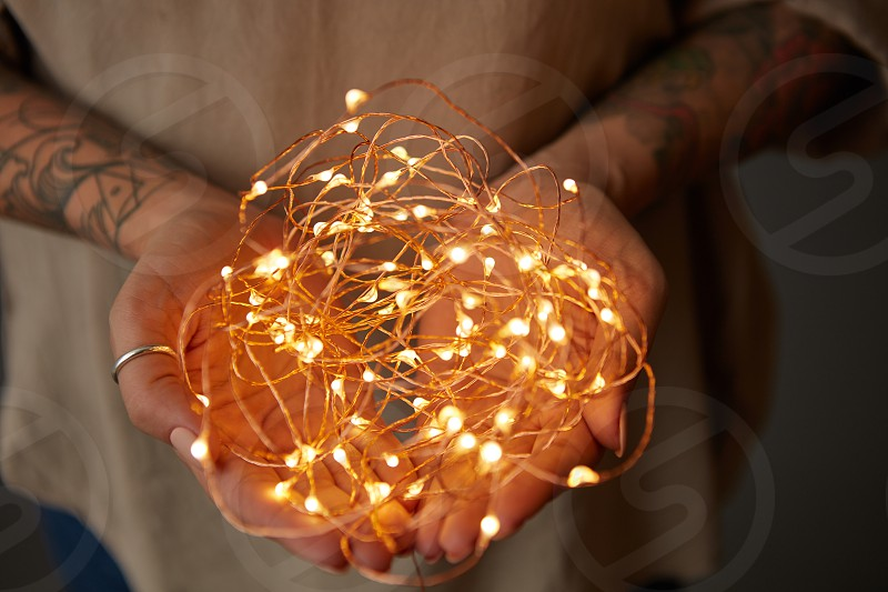 bright Christmas lights garland in female hands photo