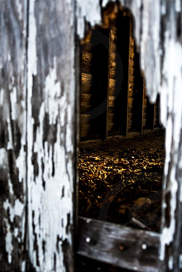 Point of view. Old doors worn with age sun set showing its golden light shining in the abandoned space through the broken wood. photo