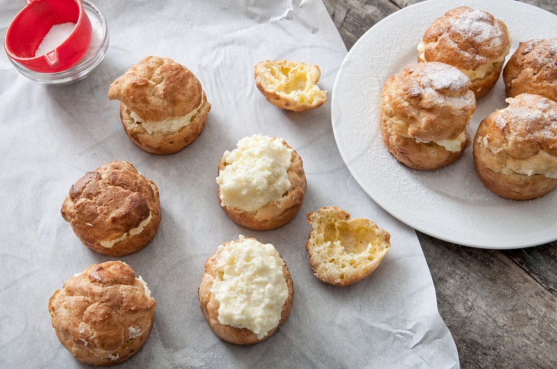 Cream puffs filled vanilla custard and dusted with icing on a table photo