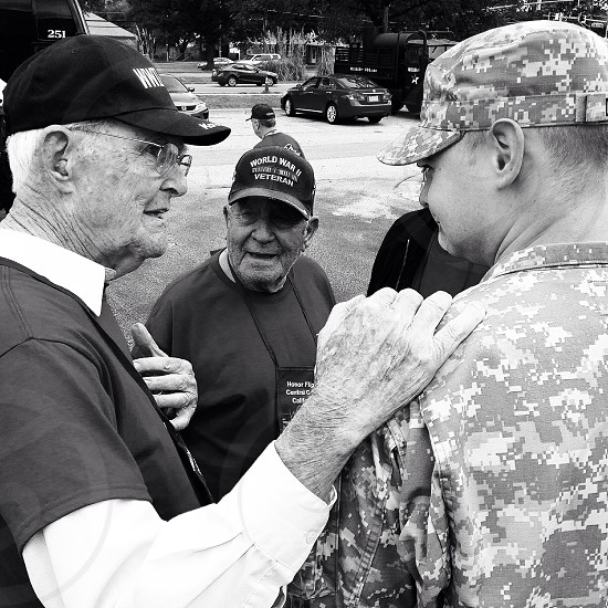 A WWII vet shares a war story with a young Army Soldier.   photo