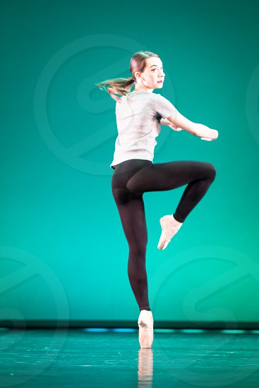 woman in black leggings dancing ballet with right knee up and left foot pointed toe on floor photo